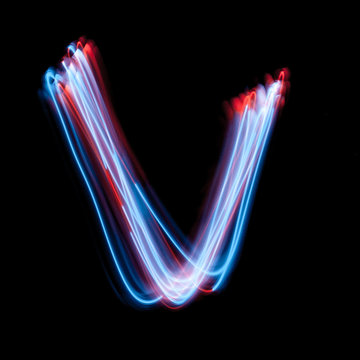 Letter V of the alphabet made from neon sign. The blue light image, long exposure with colored fairy lights, against a black background