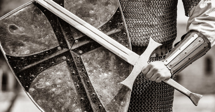Closeup view on traditional medieval knight with shield and sword. Image in black and white color style