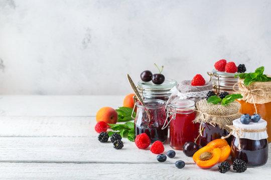Assortment of seasonal berries and fruits jams in jars