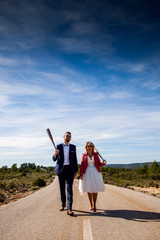 Newlywed couple hold baseball bats while strolling in an outdoor location