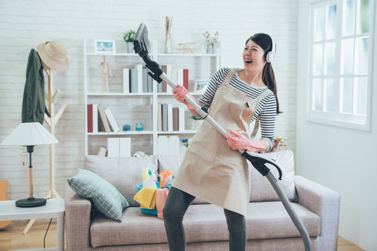 young housewife joyfully doing house chores