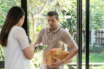Delivery service worker in uniform delivering parcel to recipient. Woman signing e-document on tablet.