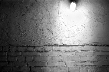 The lamp shines on the brick wall.