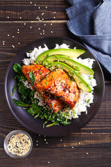 Salmon teriyaki rice bowl with spinach and avocado. View from above, top studio shot