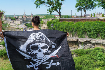 A girl looks at a castle with a pirate flag.