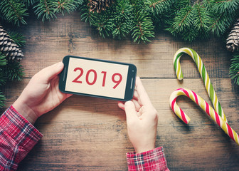 Smartphone in the child's hands with an inscription on the screen 2019, Christmas candy can and Christmas fir-tree on a wooden surface. Concept of New year.