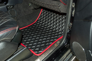 A view of a part of the interior of the car seat from leather of black color, stitched double thread of red color with contrast stitching in a vehicle interior design workshop