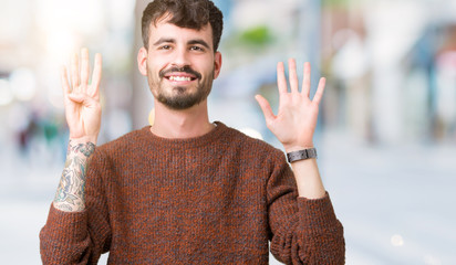 Young handsome man wearing winter sweater over isolated background showing and pointing up with fingers number nine while smiling confident and happy.