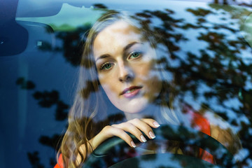 A young, beautiful woman with long hair sits at the wheel of the car and dreamingly watched through the glare of the front windshield.