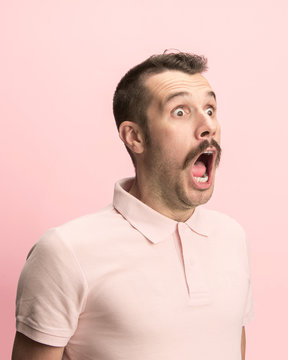 The surprised and astonished young man screaming with open mouth isolated on pink background. concept of shock face emotion