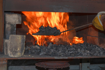 The blacksmith uses a shovel to add coals to the flame inside the forge.