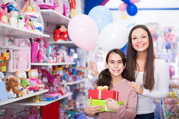 positive woman and daughter with gifts and balloons in the shop