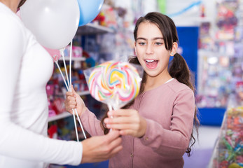 girl with balloons receives lollipop