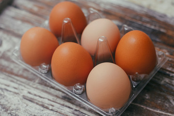 Set of six fresh brown eggs on clear plastic box. Wooden table background.