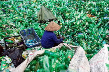 A woman sorts out recyclable soft drink plastic bottles at Xa Cau village