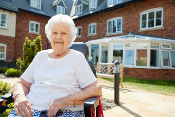 Portrait Of Senior Woman Sitting Outside Retirement Home In Motorized Wheelchair Wall mural