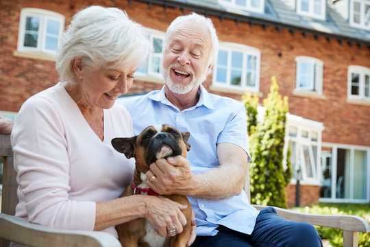 Retired Couple Sitting On Bench With Pet French Bulldog In Assisted Living Facility