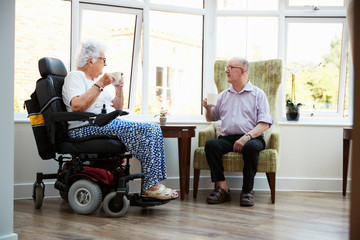 Male And Female Residents Sitting In Chairs and Talking In Retirement Home Wall mural