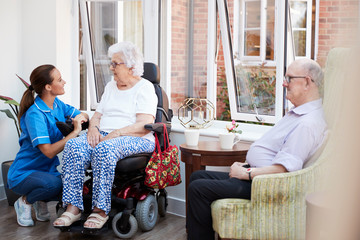 Male And Female Residents Sitting In Chair And Talking With Nurse In Retirement Home Wall mural