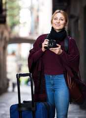 Girl holding camera in hands and photographing