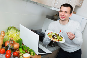 Portrait of guy sitting with notebook and salad dish