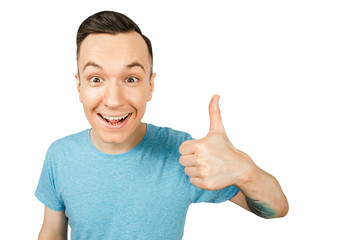 Portrait of young smiling guy showing thumb up isolated on a white background.
