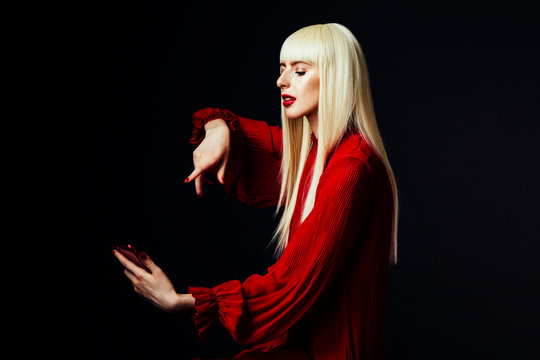 Portrait of a beautiful blonde woman looking down at a red smartphone about to press the button, isolated on black studio background