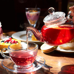 From a clear glass teapot, pour hot tea into a transparent cup. against sunlight. warm atmosphere. There are many different desserts in the background. the whole composition on the wooden table