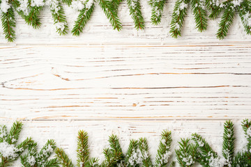 Christmas wooden background with fir branches and snow. Top view with copy space.