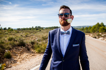 Bearded man with sunglasses and dress with suit and bow tie holds a flower with his mouth