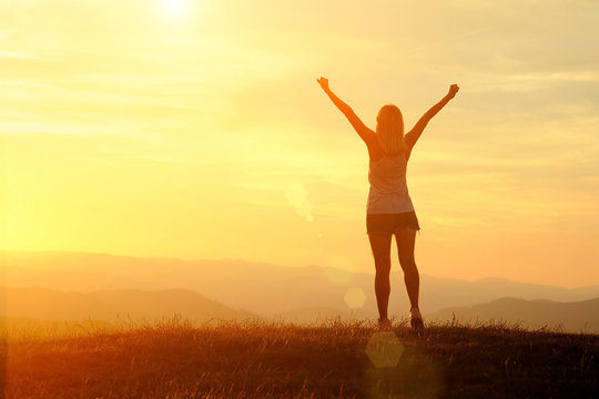 Happy woman with open arms stay on the peak of the mountain