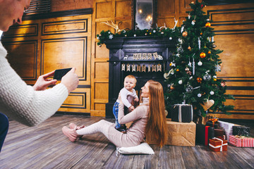 Theme mobile photography, amateur photo video phone. Hands Caucasian man holds uses smartphone makes photo mother and son home near fireplace and Christmas tree winter Christmas time New Year decor