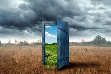 Fototapeta Creative background. Old wooden door, blue color, in the box. Transition to a different climate. The concept of climate change, portal, magic. Copy space. obraz