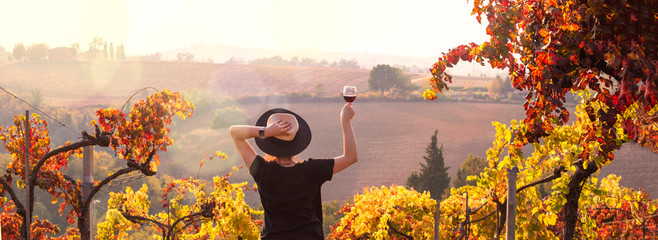 Poster Vin Girl in a hat at sunset and a glass of wine in hand. Nature Italy, hills and grape fields the sunlight. Glare and sun rays in the frame. Free space for text. Copy space.
