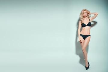 Blonde model wearing black underwear standing against light background with copyspace