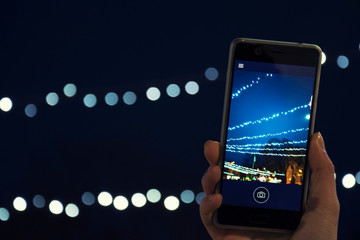 A girl photographing Christmas lights on a smartphone's camera, City, Holidays, New Year