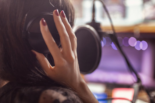 beautiful girl records a song in a professional Studio