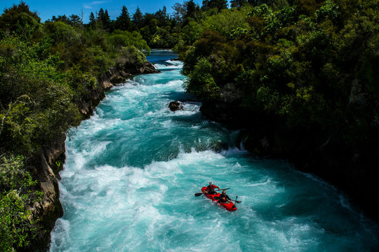 Travel New Zealand. Most popular tourist attraction Huka Falls at Lake Taupo, North Island. White and turquoise water, green forest on background. Beautiful landscape view. Active summer holidays.