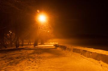 Winter misty embankment in the light of lanterns