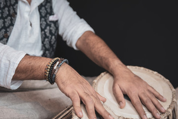 Images of a man's hands (wearing beads) playing the Tabla - Indian classical music percussion instrument - black background.