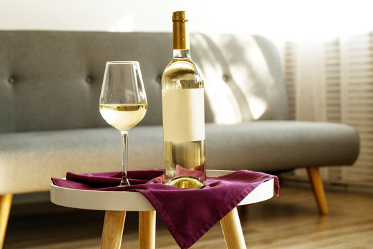 Vintage bottle of white wine with blank matte label and poured glass on purple napkin, lofty interior background. Expensive bottle of shardonnay concept. Copy space, top view, flat lay, close up.