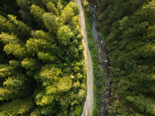Road through mountains and forest captured from above