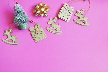 Christmas tree, decorative deer figurines, gold bow, gift boxes on a pink background. Flat lay New Year photo