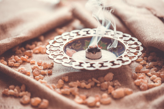Frankincense burning on a hot coal. Frankincense is an aromatic resin, used for religious rites, incense and perfumes, incense smoke (color toned image)