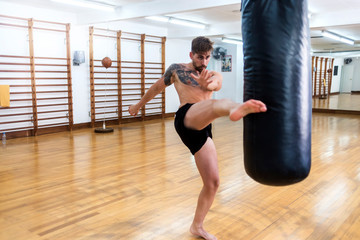 Male boxer workout high kick on the punching bag in gym.