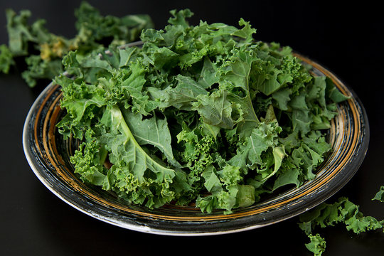 Fresh green curly kale leaves on black board, isolated. Healthy food.