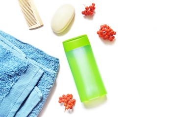 Organic spa cosmetics. Flat lay blue towel, comb, soap, green shampoo bottle and rowan