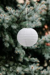 White lamp lampion on green christmas tree