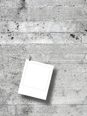 Blank square instant photo frame against grey concrete wall background