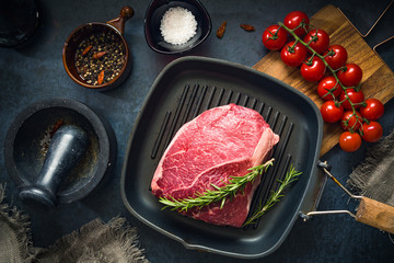 Deurstickers Vlees Raw Fresh Marbled Meat Beef on a grill pan ready for cooking on a blue concrete background top view.